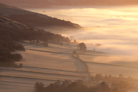 Early morning mist swirls around the base of Compton Hill and Wavering Down in Somerset.  Just visible through the mist is Compton Bishop village surrounded by fields enclosed with traditional hedgerows.  Part of the Mendip Hills AONB.