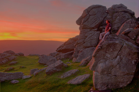 'Eventide' – climber Jon Hawker enjoying the afterglow light from the edge of a plutonic boulder at Bonehill, in Dartmoor National Park