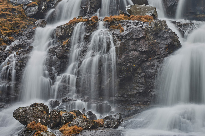 Close-up of one of many waterfalls around Fuglafjørður, shot from the back seat of the car.