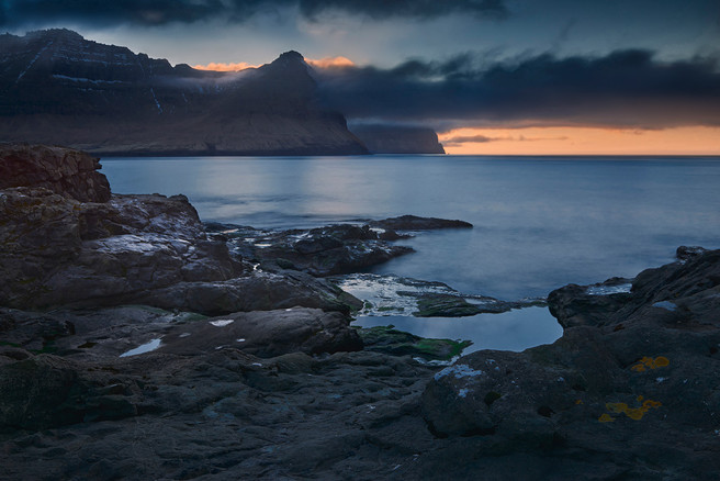 The island of Kunoy seen from the rocky shore of Viðareiði at the last light of the day.